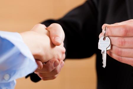 broker: Dos hombre de negocios dándose la mano, las manos sólo para ser visto y una clave que se da