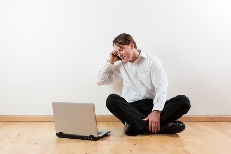 crosslegged: Man sitting cross-legged on the wooden floor of his apartment with laptop and is making a phone call