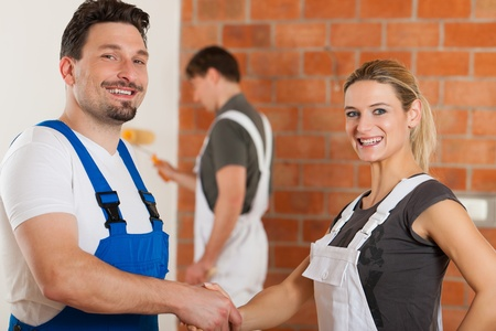 Three people - one woman and two men - renovating an apartment; the couple in front are shaking hands photo