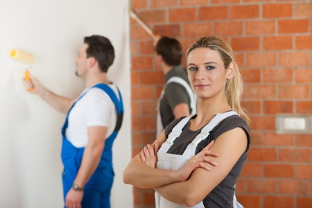 Three people - one woman and two men - renovating an apartment; the woman is standing with arms crossed in front photo