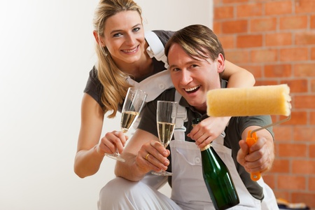 Young couple moving in new flat doing renovation and painting, celebrating their new home with sparkling wine photo