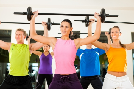 fitness club: Group of five people exercising using barbells in gym or fitness club to gain strength and fitness