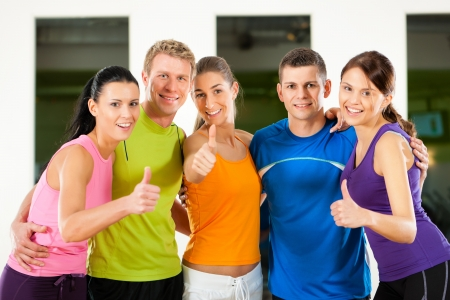 training group: Group of five people exercising in gym or fitness club