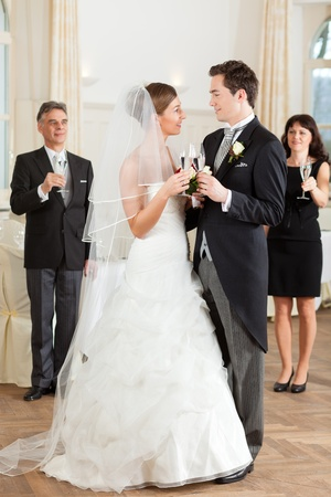 Bridal couple clinking glasses while the guests standing in the background photo