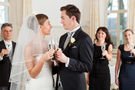 zeugnis: Brautpaar Gl�ser klirren, w�hrend die G�ste im Hintergrund stehen Lizenzfreie Bilder