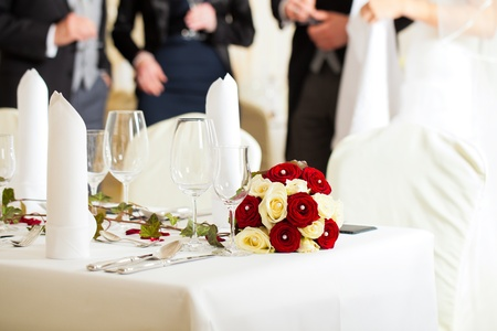 setup man: Wedding table at a wedding feast decorated with bridal bouquet