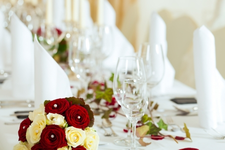 wedding reception: Wedding table at a wedding feast decorated with bridal bouquet