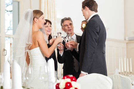 witness: Wedding party bride, groom and bride father clinking glasses with sparkling wine