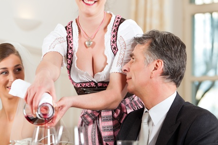 wedding guest:  Wedding party at dinner - wine is be poured into glasses  Stock Photo