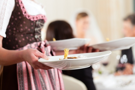 Wedding party at dinner - the dish is going to be served photo