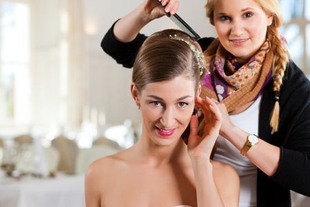 Stylist pinning up a bride's hairstyle before the wedding photo