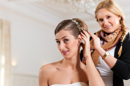 chignon: Stylist pinning up a brides hairstyle before the wedding Stock Photo