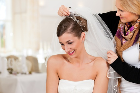wedding hairstyle: Stylist pinning up a brides hairstyle and bridal veil before the wedding Stock Photo