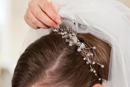 Stylist: Estilista fijando al peinado de una novia y velo de novia antes de la boda