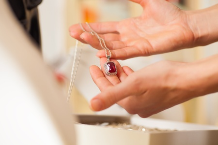 jewelry store: Female jeweller or designer presenting jewellery in her store Stock Photo