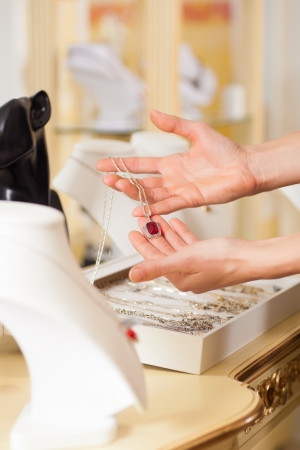Female jeweller or designer presenting jewellery in her store Stock Photo - 11840614