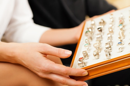 Couple choosing wedding rings at a jeweller photo
