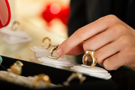 Couple - only hand of woman to be seen - choosing wedding rings at a jeweller photo