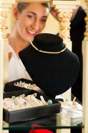 jewelry store: Woman at the jeweller is looking for jewellery