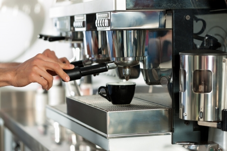 man machine: Barista prepares cappuccino in his coffeeshop; close-up