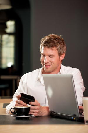 Couple in coffeeshop with laptop and mobile; only the man is to be seen Stock Photo - 11840786