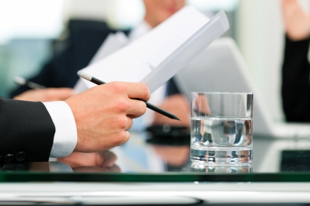 law: Business - meeting in an office; lawyers or attorneys discussing a document or contract agreement