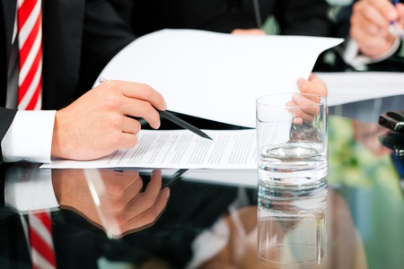 law office: Business - meeting in an office; lawyers or attorneys discussing a document or contract agreement