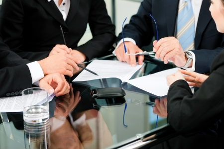 counsel: Business - meeting in an office; lawyers or attorneys discussing a document or contract agreement