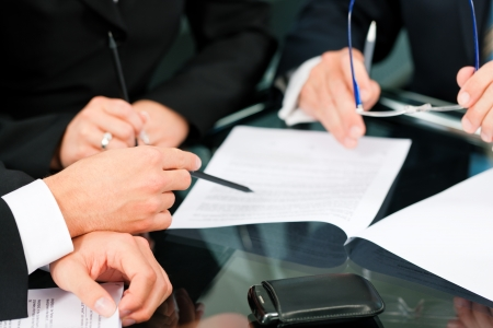 business law: Business - meeting in an office; lawyers or attorneys discussing a document or contract agreement