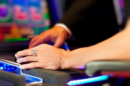 Couple in Casino on a slot machine winning and having fun - only hands to be seen photo