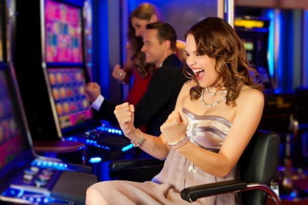 man machine: Friends in Casino on a slot machine; all obviously are winning Stock Photo