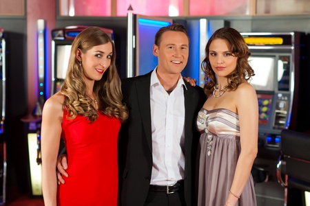 ARCADE GAMES: Three friends - one man and two women - in Casino in a playful mood