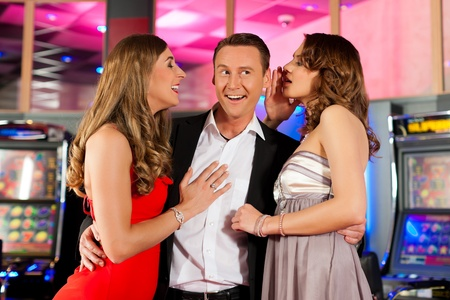 automat: Three friends - one man and two women - in Casino in a playful mood