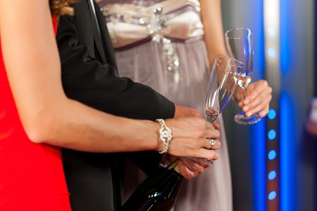 Three friends with champagne in a bar or casino - only torsos to be seen Stock Photo - 11840863