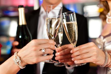 brindisi champagne: Tre amici con champagne in un bar o casino - torsi solo da vedere