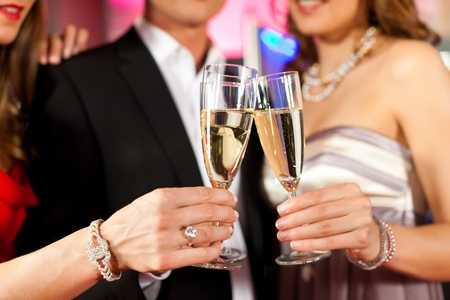 Three friends with champagne in a bar or casino - only torsos to be seen photo