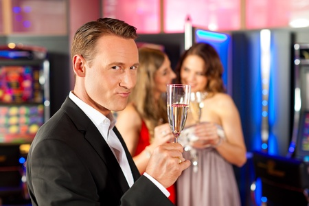 Three friends with champagne in a bar or casino, a man is looking in the camera photo