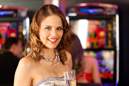 automat: Friends in Casino on a slot machine; a woman is looking into the camera