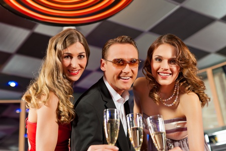 People with champagne in a bar or casino having lots of fun photo