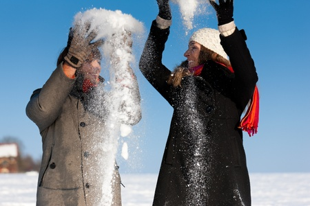Couple - man and woman - having a winter walk and throwing snow Stock Photo - 11840797
