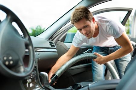 cleaning car: El hombre es pasar la aspiradora o limpiar el neum�tico del coche Foto de archivo
