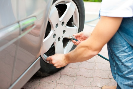 hubcap: Man - only hand to be seen - is controlling the tire pressure of his car