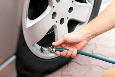 Man - only hand to be seen - is controlling the tire pressure of his car photo