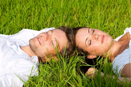Happy couple lying on a meadow in summer photo