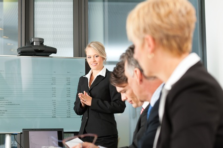 tax consultants: Business - presentation within a team; a female, colleague is standing on the screen