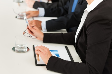 Business - people sitting in a meeting, close-up on hands and woman in the front photo