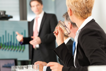 Business - presentation within a team; a male, colleague is standing on the screen photo