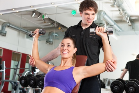 health club: Young couple exercising in gym with weights, one of them is personal trainer