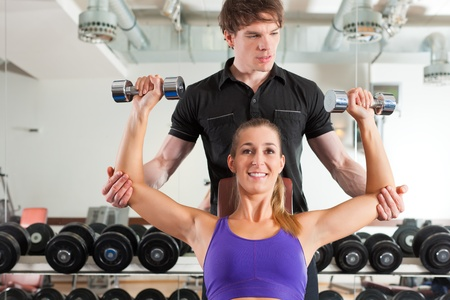 personal trainer: Young couple exercising in gym with weights, one of them is personal trainer