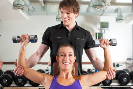 Young couple exercising in gym with weights, one of them is personal trainer photo
